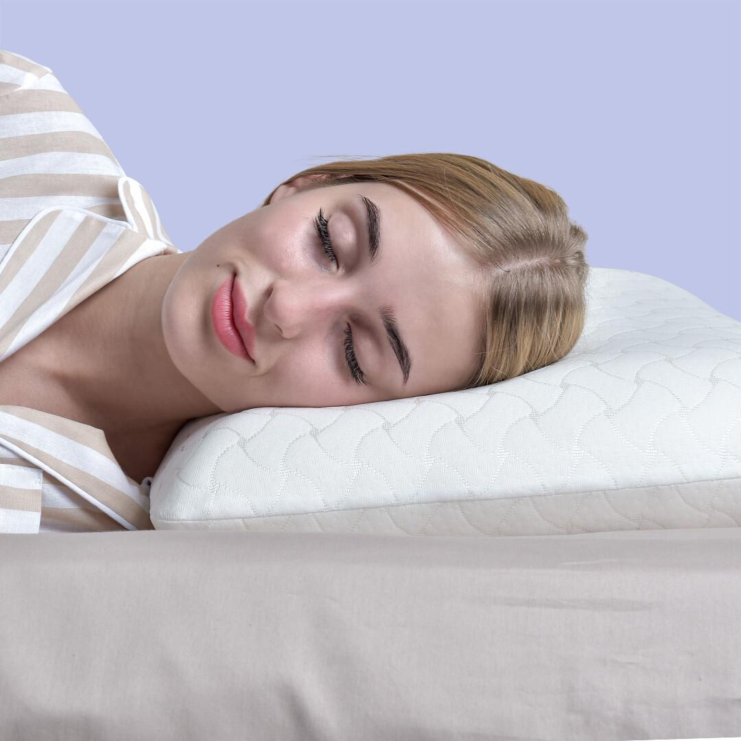 Голова девушки лежит на белой ортопедической подушке